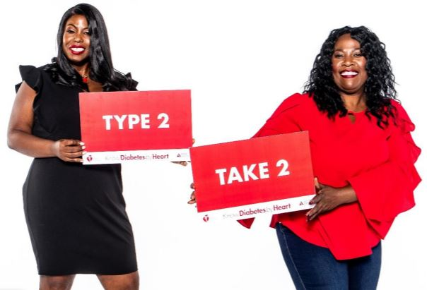 Two women holding Type 2 Take 2 signs