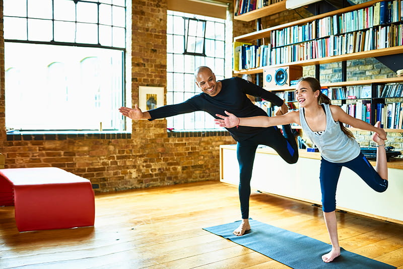 father and daughter do yoga in apartment