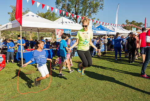 HeartWalk participant jumping rope with a young girl