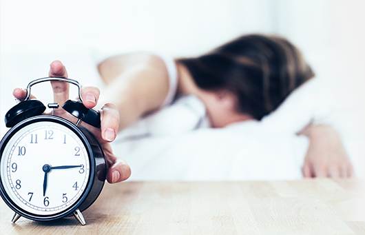 Girl in bed out of focus reaching to turn off alarm clock