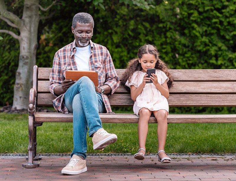 grandfather and child looking at mobile devices
