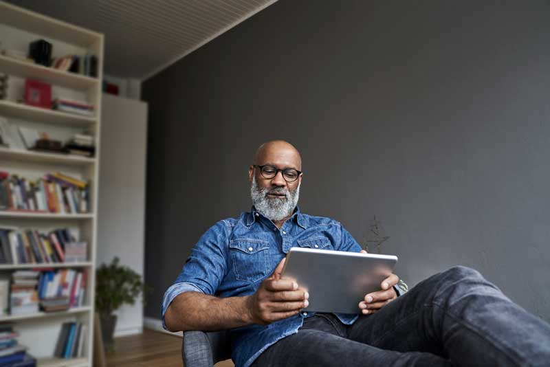 Man relaxing at home with his tablet