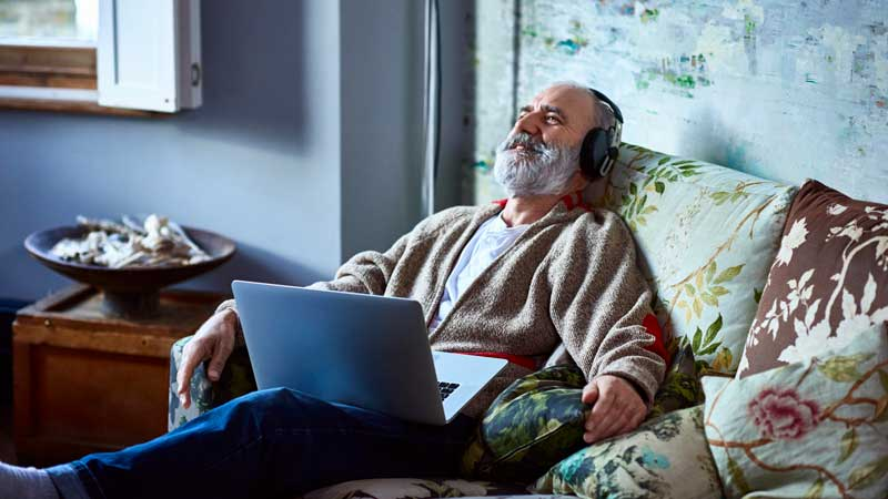 Older man relaxing on couch with headphones