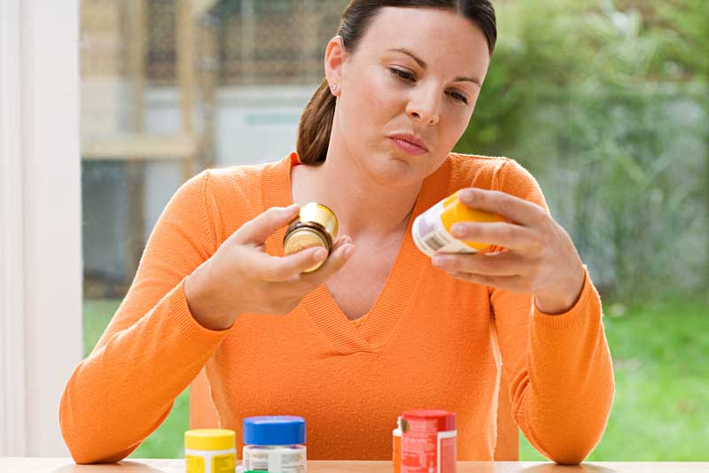 woman reading labels on pill bottles