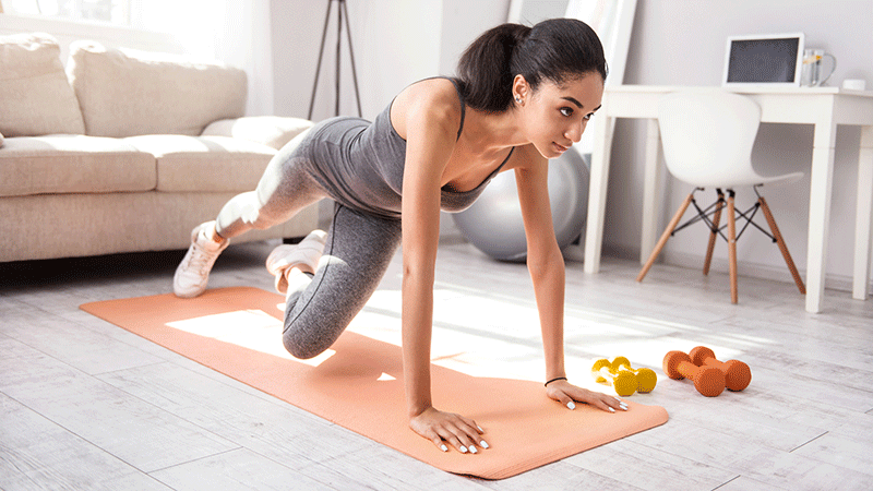 Woman exercising on mat with weights near