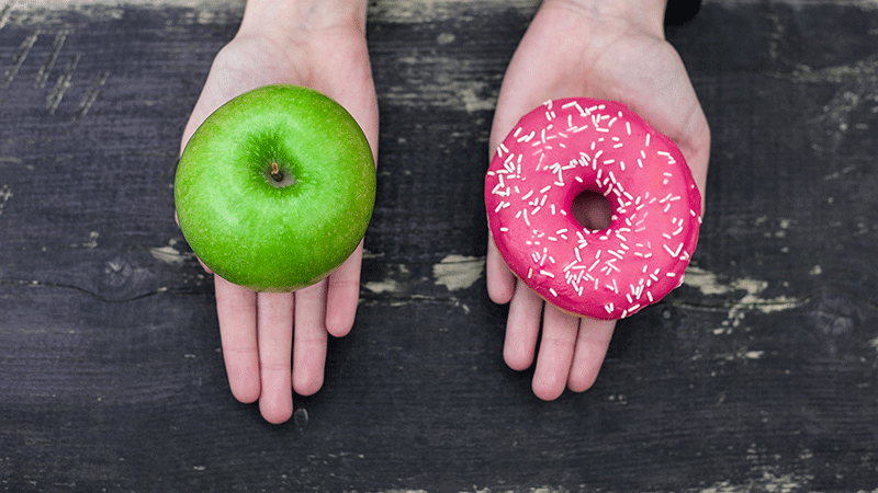 Hands showing choice between an apple or donut