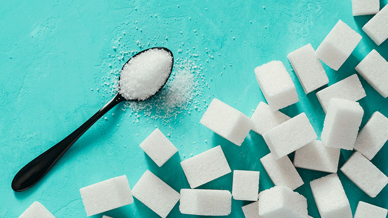 Sugar cubes and sugar in spoon. White sugar on turquoise background