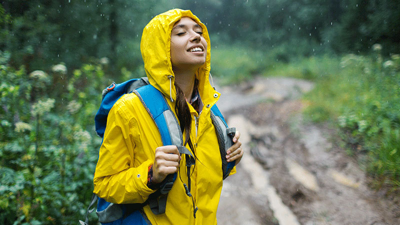 Young woman in raincoat enjoys nature in the rain