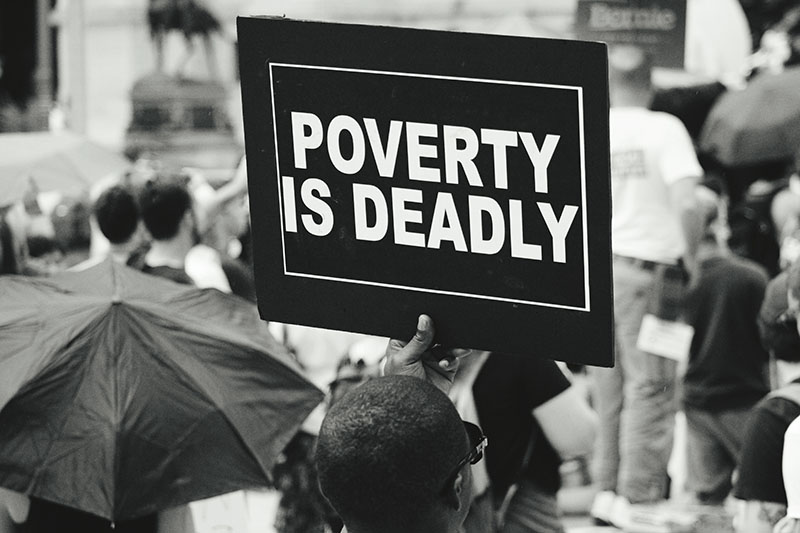 Man holding a poverty is deadly sign